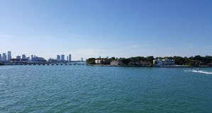 Tropical landscape of Miami tourist coast in a sunny day. Travel and tourism in United States, nature and ocean, blue water and waves, blue sky, buildings in a royalty free stock images