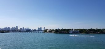Tropical landscape of Miami tourist coast in a sunny day. Travel and tourism in United States, nature and ocean, blue water and waves, blue sky, buildings in a royalty free stock photos