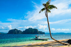 Tropical landscape. With mountain islands, palm tree and lonely boat Royalty Free Stock Images
