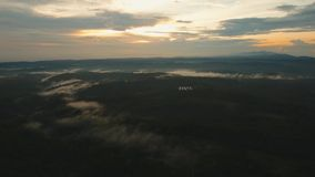Tropical landscape at sunset, Bali,Indonesia. Aerial view of forest, mountains with fog, clouds at sunset on Bali,Indonesia. Tropical rainforest, trees, jungle stock footage