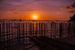 Tropical landscape at sunset. The fence and the sea. White beach. Boracay. Philippines. Royalty Free Stock Image