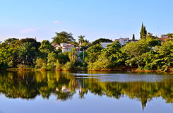 Tropical landscape with trees, lake, blue sky and reflection in water Stock Photo