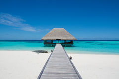 Tropical landscape with wooden bridge and house on the water at Maldives Royalty Free Stock Image