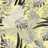 Tropical leaf design with dark, light gray palm trees and leaves of a Monstera plant on a yellow background. Royalty Free Stock Photo