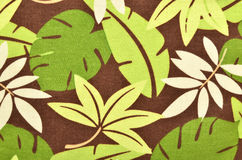 Tropical leaves pattern on brown fabric. Royalty Free Stock Photos