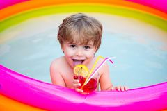 Tropical lemonade. Beverage. Summer holiday. A child in the pool with a cocktail. Vacation. Trip to the resort. Happy royalty free stock photos