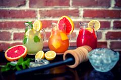 Tropical lemonades in jugs at restaurant or bar with fruits and Royalty Free Stock Photo