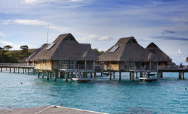 Tropical lodges over the sea and ladders in water. Royalty Free Stock Photo