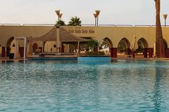Tropical luxury hotel resort building with pool bar. Scenic morning landscape with empty swimming pool. Famous touristic place and travel destination in Egypt royalty free stock photos