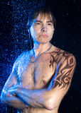 Tropical man. Wet Man in Aqua Studio. Close-up portrait of handsome man with graphic brown water-resistant tattoo on shoulder and neck, strong arms crossed on Stock Photos