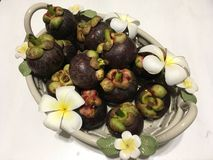 Tropical mangosteen fruits in ceramic basket, decorated with frangipani flowers. Serene peaceful green joy meditation aesthetic colourful countryhome homedecor royalty free stock photos