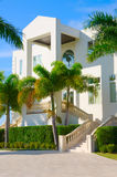 Tropical mansion luxury vacation house w palm trees. Beautiful luxury residential home with front stairways and lush green palm trees against a blue morning sky Stock Photo
