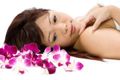 Tropical Model. A young Asian woman lying on the floor with purple orchid flowers Royalty Free Stock Photos