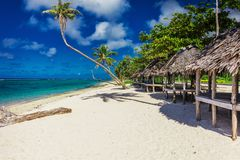 Tropical natural beach on Samoa Island with palm trees and woode. Tropical vibrant natural beach on Samoa Island with palm trees and wooden fales, Upolu Royalty Free Stock Photos