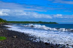 Tropical ocean waves splashing onto lava rock shoreline Stock Photo