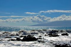 Tropical ocean waves splashing onto lava rock shoreline Stock Image