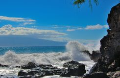 Tropical ocean waves splashing onto lava rock shoreline Royalty Free Stock Images