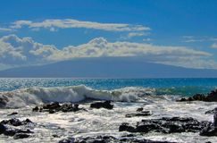 Tropical ocean waves splashing onto lava rock shoreline Stock Photo