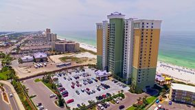 Tropical oceanfront vacation resort hotel by the beach. Aerial of a vacation resort waterfront hotels by the ocean with recreation attractions on a hot, bright stock footage