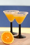 Tropical Orange Drinks. Orange juice drinks with sugared rims and fresh orange - focus on orange slice to front royalty free stock photography