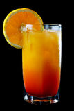 Tropical orange and rum cocktail. Closeup of a glass of iced tropical orange and rum cocktail garnished with a slice of fresh orange over a black background stock photography