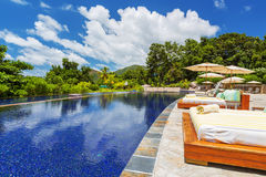 Tropical outdoor swimming pool and sun loungers Royalty Free Stock Photos