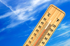 Tropical outdoor temperature on the thermometer. Tropical temperature of 35 degrees Celsius, measured on an outdoor thermometer-In the background clear sky with Royalty Free Stock Image