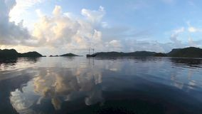 Tropical Pacific Scenery. Calm seas surround an Indonesian Pinisi schooner in Raja Ampat, Indonesia, at sunset. This region is popular among diverse because of stock footage