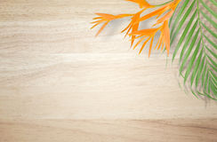 Tropical palm tree leaf and Bird of paradise flower on  wooden b Royalty Free Stock Photo