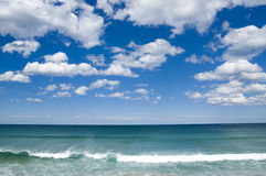 Tropical Paradise. A turquiose blue ocean meeting a vivid blue sky with puffy white clouds Stock Photos