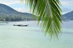 Tropical paradise - closeup of palm leaf and turquoise sea water. With longtail boats and green hills behind it Stock Photo