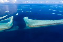 Maldives atolls and coral reefs view from a seaplane. Calm blue sea and sandbanks. Royalty Free Stock Image