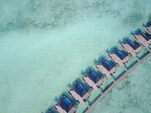 Tropical paradise resort on a sunny day. Maldives - Jul 29, 2017: Aerial view of a tropical paradise resort on the edge of a coral reef on a sunny day stock photos