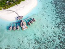 Tropical paradise resort on a sunny day. Maldives - Jul 29, 2017: Aerial view of a tropical paradise resort on the edge of a coral reef on a sunny day royalty free stock image