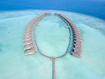 Tropical paradise resort on a sunny day. Maldives - Jul 29, 2017: Aerial view of a tropical paradise resort on the edge of a coral reef on a sunny day stock image