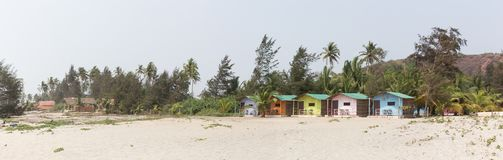 Tropical paradise is a sandy beach with colorful bungalows. Stock Photos