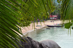Tropical paradise - sandy beach and longtail boat behing rocks a. Nd palm tree leaves Royalty Free Stock Photos
