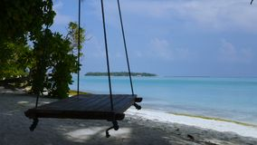 Beautiful beach of Maldives with a swing. Tropical Paradise with turquoise sea, white sand, palm trees and blue sky. Beautiful beach of Maldives with a swing stock footage
