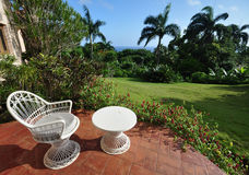 Tropical Patio. Garden patio at resort in the Dominican Republic offers guests a peaceful retreat. White wicker seat and table set on red terra cotta tiles Royalty Free Stock Image