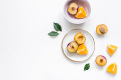 Tropical peach and orange fruits for fresh juice on plates white background top view space for text Stock Photos