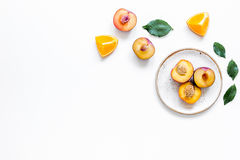 Tropical peach and orange fruits for fresh juice on plates white background top view space for text Royalty Free Stock Image