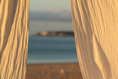 Tropical Perspective. Is there anything more tropical than the idyllic vista of hanging cabana curtains overlooking sun, sand and ocean paradise Royalty Free Stock Photography