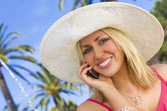 Tropical Phonecall. An absolutely gorgeous blond haired blue eyed woman makes a phonecall on her mobile surrounded by palm trees in city square as a fountain Royalty Free Stock Photos