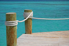 Tropical pier. Two posts connected with rope. Emerald tropical sea Stock Photography