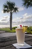 Pina Colada. A tropical pina colada drink with pineapples and cherry with palm tree in the background Stock Images