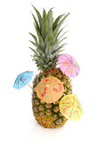 Tropical pineapple with cororful umbrellas Stock Photography