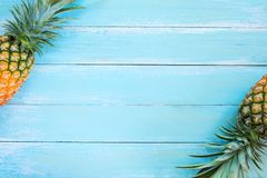 Tropical pineapple on wood plank blue color. Frame layout summer vacation background concept royalty free stock photo