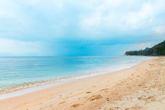 Tropical rain clouds on the calm sea and deserted beach Stock Photography