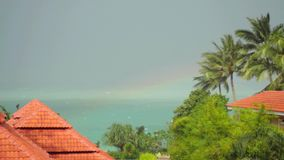 Tropical rain drops falling on roof of the houses in island Koh Samui, Thailand. Seaview and rainbow. 3840x2160 stock footage