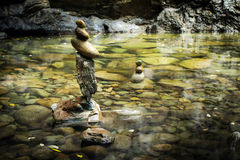 Tropical rain forest landscape with lake and balancing rocks. Amazing tropical rain forest landscape with lake and balancing rocks tower for zen meditation royalty free stock images